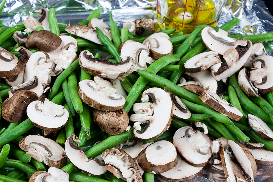 Roasted Green Beans and Mushrooms - cleaned and diced green beans and mushrooms on a foil lined baking sheet