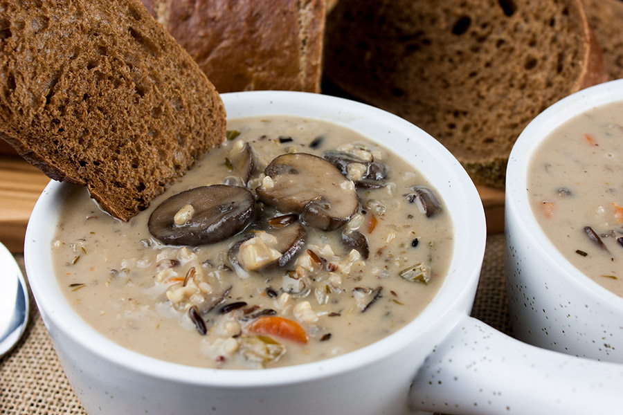wild rice and mushroom soup in white crock with brown bread