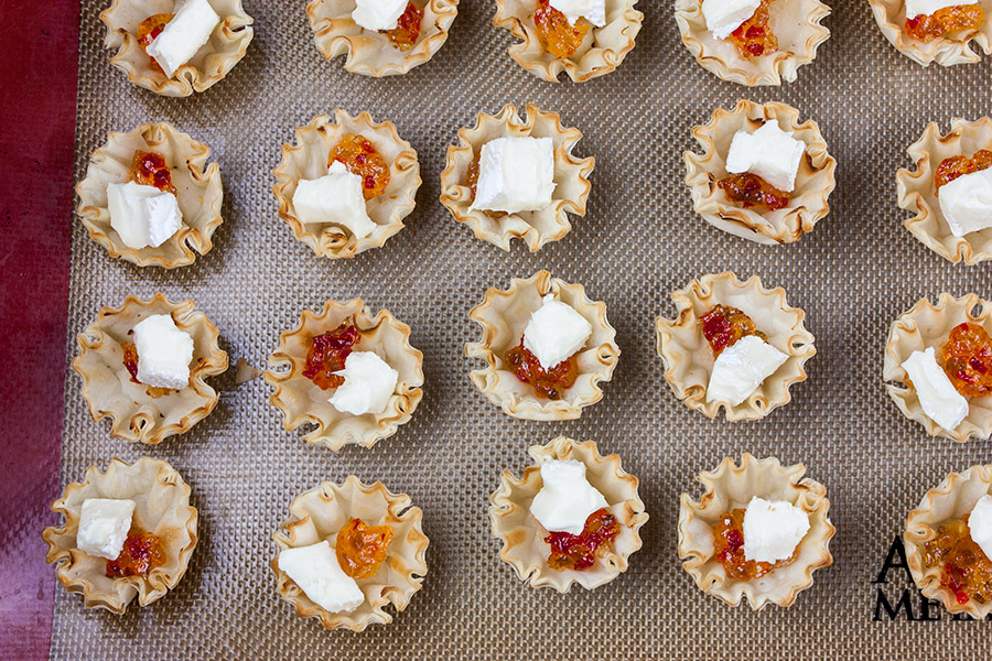 phyllo shells filled with pepper jelly and brie cubes on silpat lined baking tray