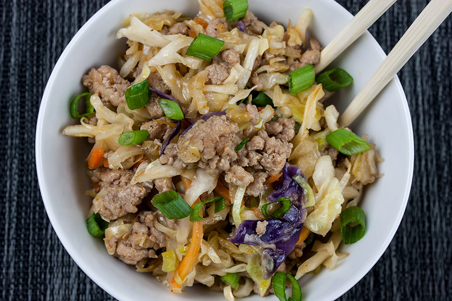 pork egg roll bowl in white bowl with chop sticks