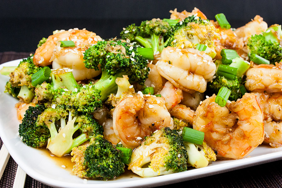 shrimp and broccoli stir fry on white platter garnished with sesame seeds and diced green onions
