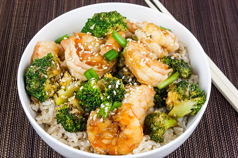 shrimp and broccoli stir fry served in white bowl over brown rice garnished with sesame seeds and diced green onions
