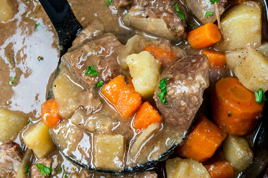 beef stew in a ladle over top of the slow cooker