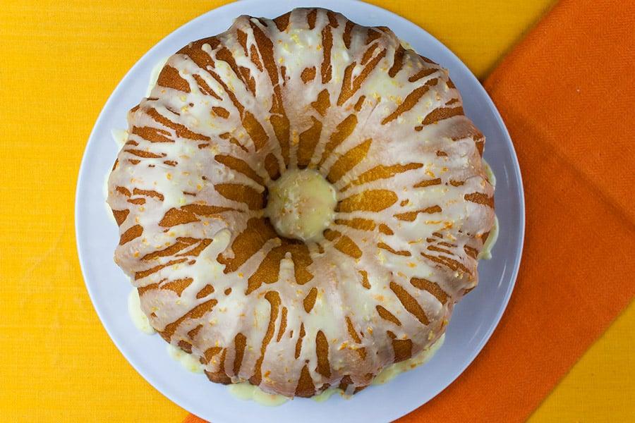 Lemon-Orange Pound Cake drizzled with glaze on white plate with yellow and orange background