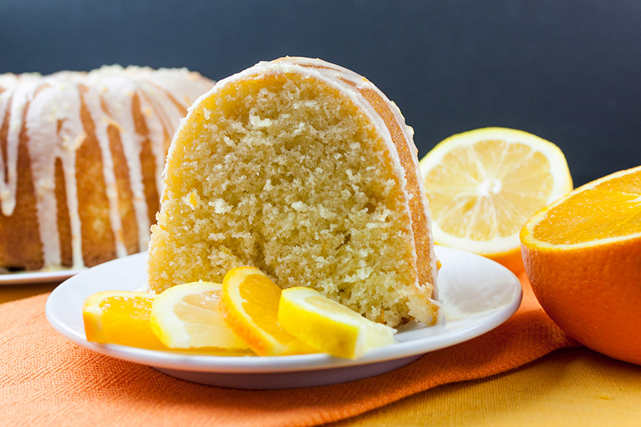 slice of the Lemon-Orange Pound Cake on white plate with slices of fresh lemon and orange