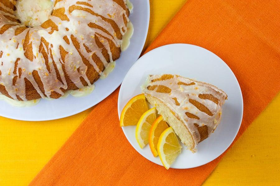 slice of lemon orange pound cake on white plate garnished with citrus slices