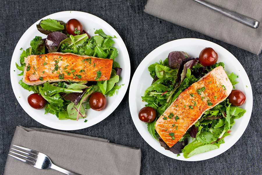 Pan-Seared Salmon Salad with Lemon Vinaigrette on white plates with gray napkins and forks