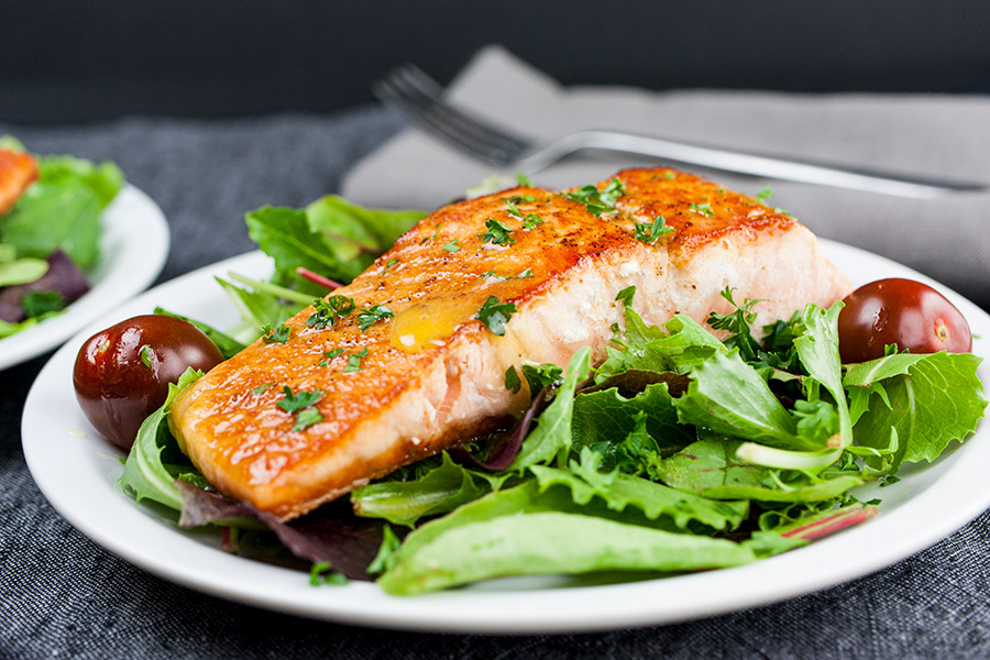 Pan-Seared Salmon Salad with Lemon Vinaigrette on white plate black background