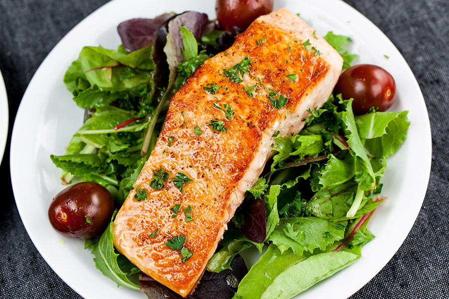Pan-Seared Salmon Salad with Lemon Vinaigrette on white plate with black background