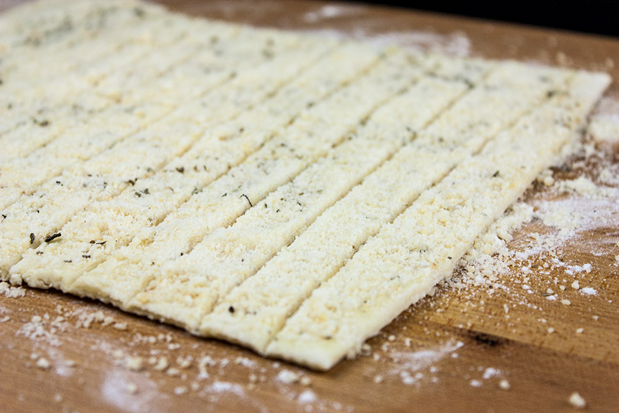 Puff Pastry on cutting board sprinkled with Parmesan, Gruyere, garlic, and herbs sliced into strips