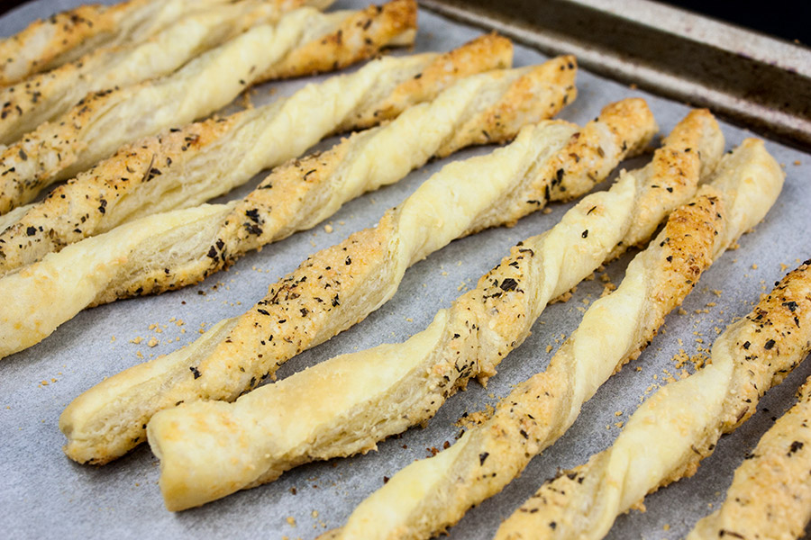 baked Puff Pastry Parmesan Cheese Straws on a parchment lined baking sheet