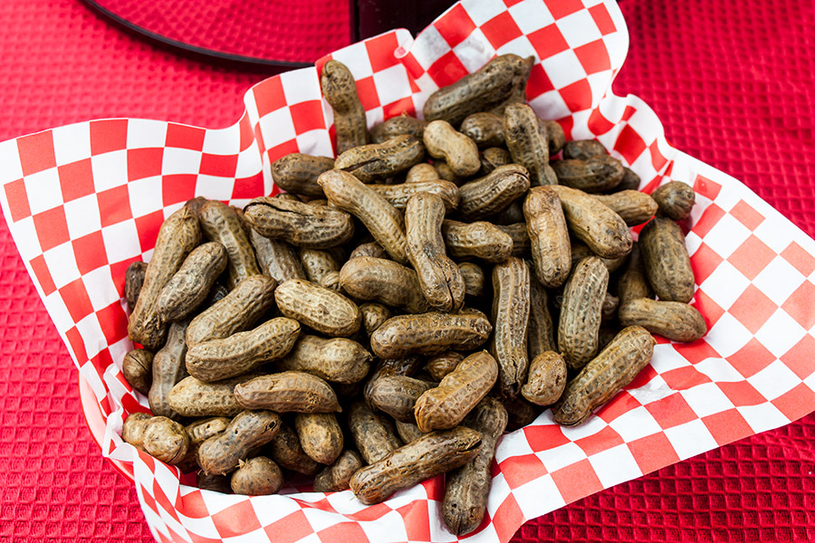 boiled peanuts in red basket with red and white checkered paper liner in front of a slow cooker