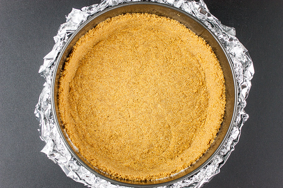 graham cracker crust in a springform pan with heavy-duty foil wrapped tightly around the pan