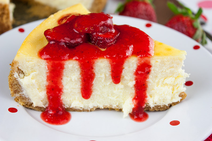 close up of Smooth and Creamy Cheesecake drizzled with fresh strawberry coulis