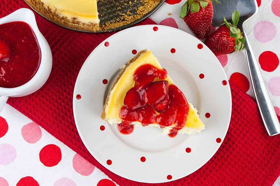 Smooth and Creamy Cheesecake on white plate with red dots drizzled in fresh strawberry coulis