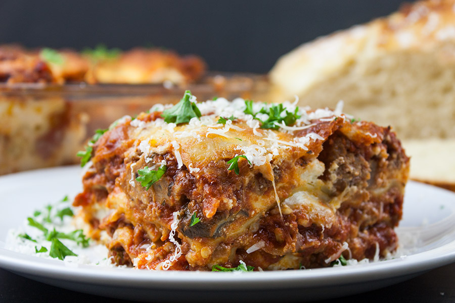 Absolute Best Ever Lasagna serving on a white plate garnished with parsley and Parmesan cheese