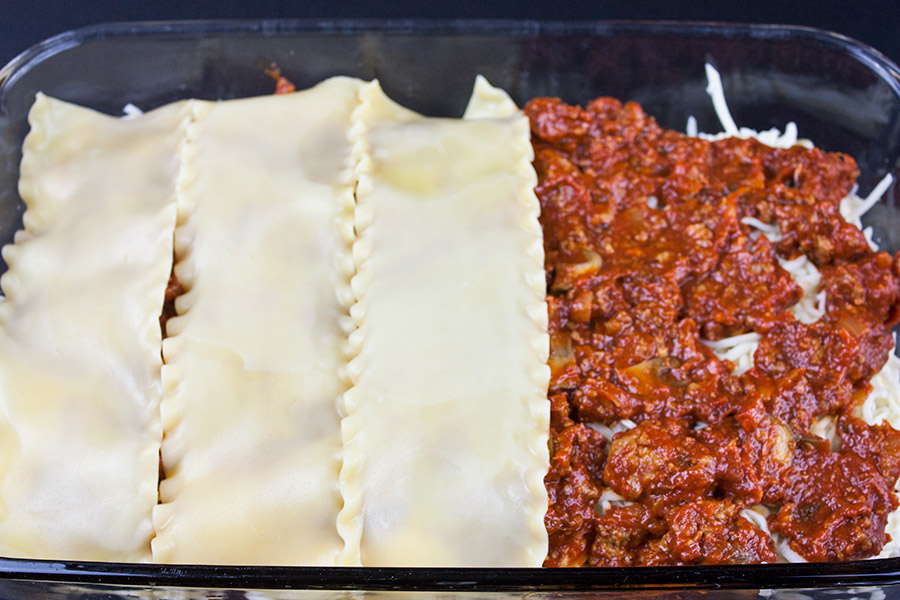 Lasagna layering in the glass pan showing vertical noodle layering