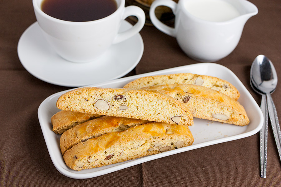 Almond Biscotti on white plate with coffee and cream pitcher