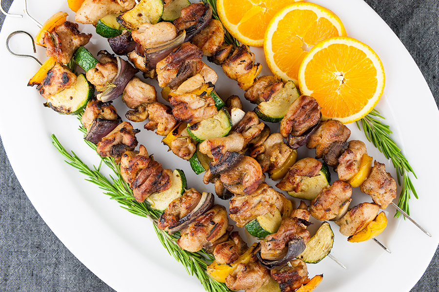 Orange Rosemary Chicken Kebabs on white platter garnished with orange slices and fresh rosemary