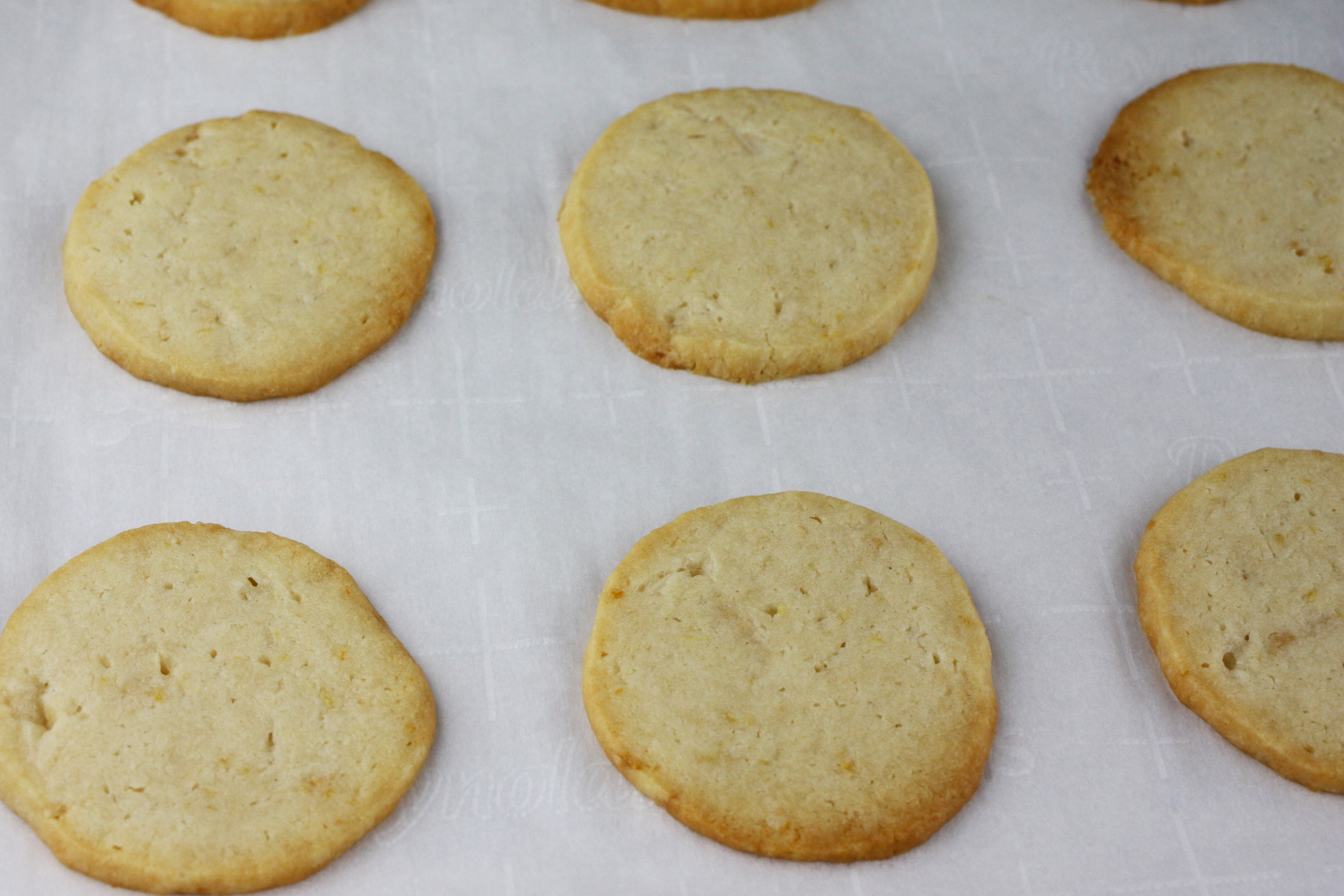 baked Lemon Sandwich Cookies on cookie sheet lined with parchment paper