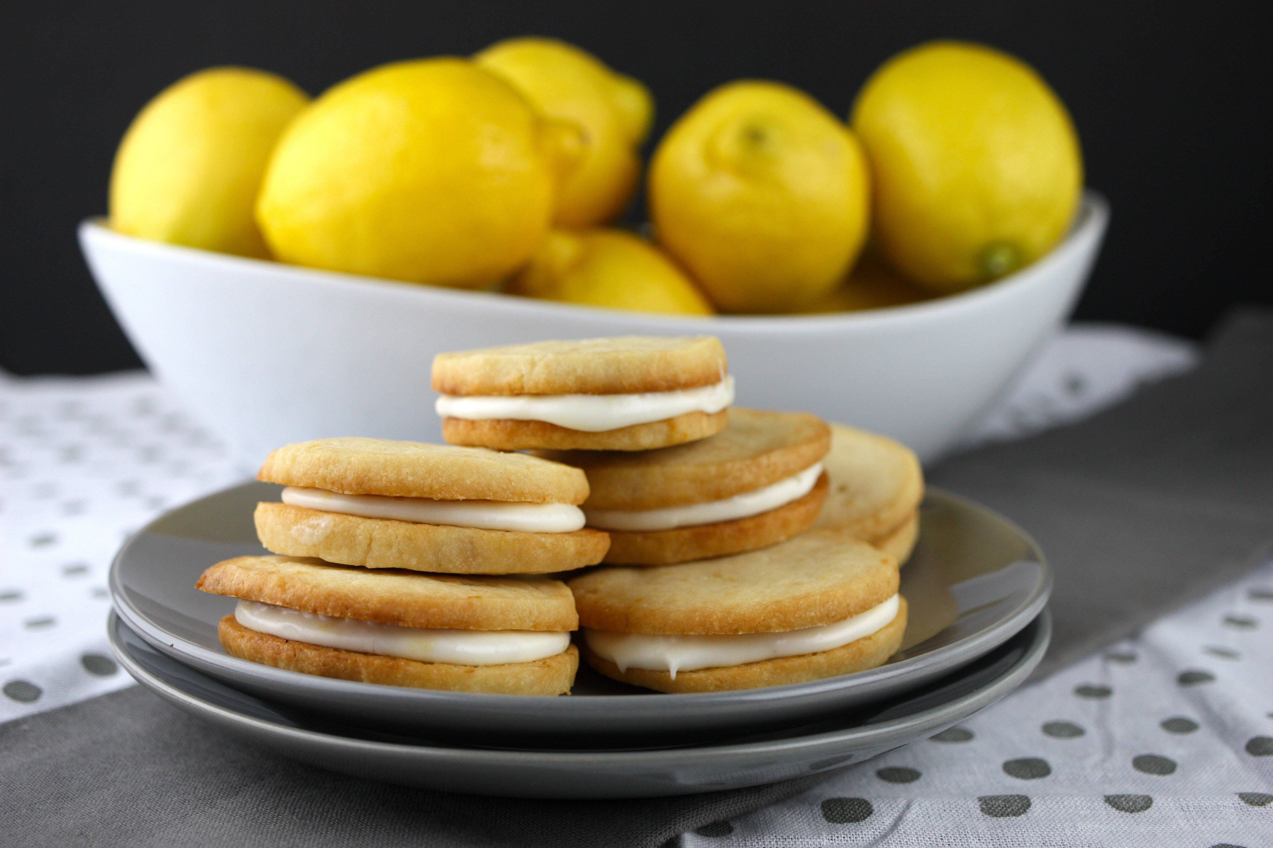 Lemon Sandwich Cookies stacked on gray plate in front of a white bowl of lemons