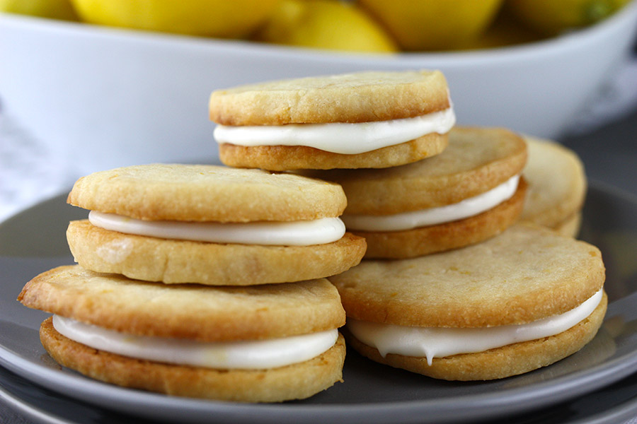 close up of Lemon Sandwich Cookies stacked on gray plate