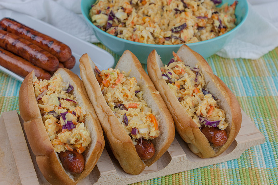 Hot Dogs with Mustard Slaw on a wooden hot dog board with bowl of mustard slaw in background and platter of grilled hotdogs