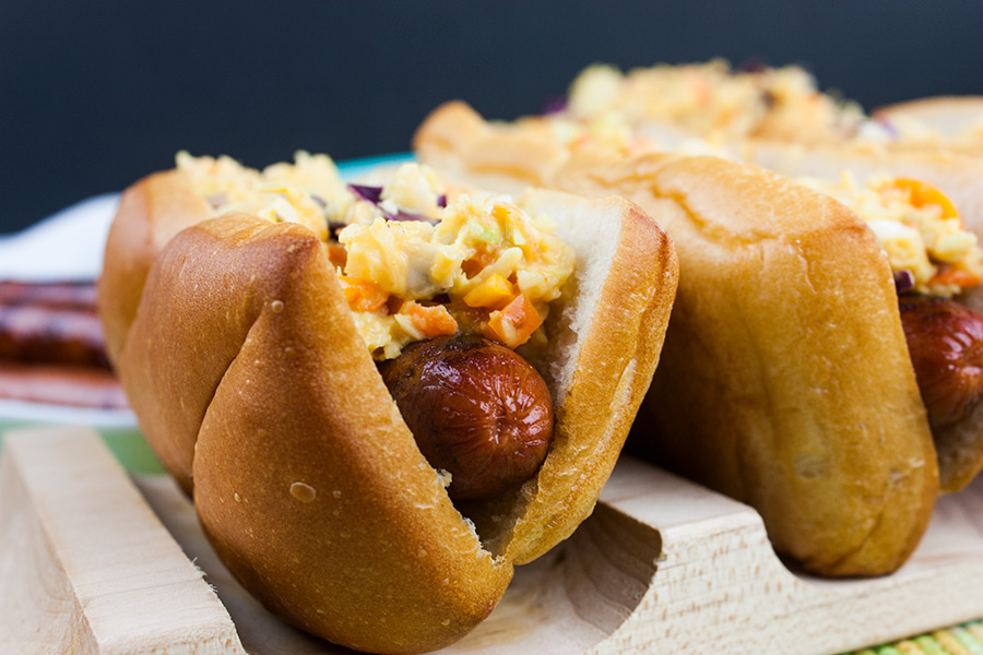 Hot Dogs with Mustard Slaw on a wooden hot dog board